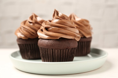Delicious fresh chocolate cupcakes with cream on white table, closeup