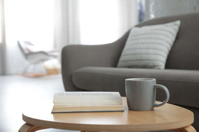 Book and cup of coffee on table near sofa. Interior design