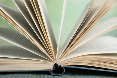 Open book on blue wooden table against blurred green background, closeup
