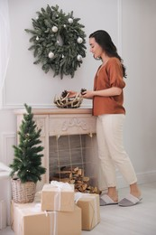 Woman decorating home interior with conifer cones