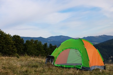 Color camping tent on grass in mountains, space for text