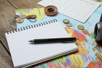 Different travel accessories on wooden table, closeup. Planning summer vacation trip