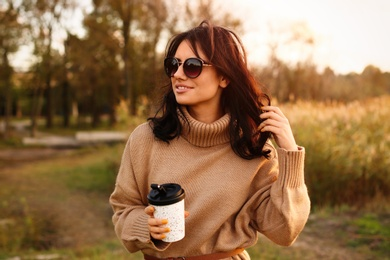 Beautiful young woman with cup of coffee wearing stylish autumn sweater outdoors