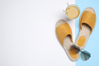 Stylish shoes, sunglasses and glass of juice on color background, flat lay with space for text. Beach objects