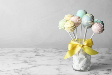Sweet cake pops on white marble table against grey background. Space for text