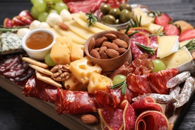 Assorted appetizers served on black wooden table, closeup
