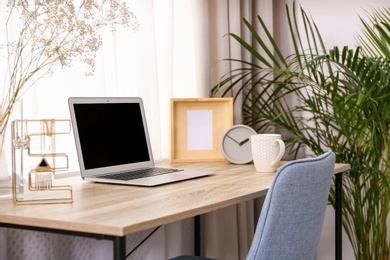 Stylish workplace interior with laptop on wooden table near window