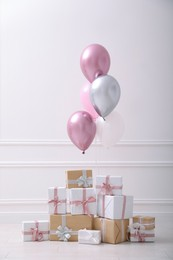 Many gift boxes and balloons near white wall in room