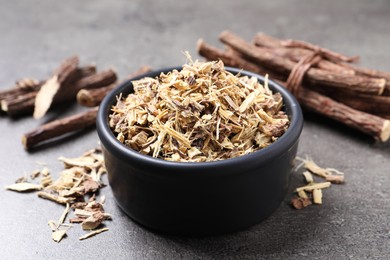 Dried sticks of liquorice root and shavings on grey table