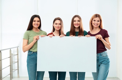 Portrait of happy ladies with empty poster indoors, space for text. Women power concept