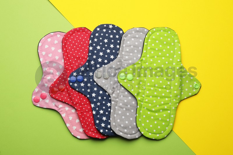 Many reusable cloth menstrual pads on color background, flat lay