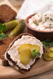 Sandwich with delicious lard spread and pickles on wooden table, closeup