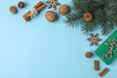 Flat lay composition with fir branch and gift box on light blue background, space for text. Winter holidays