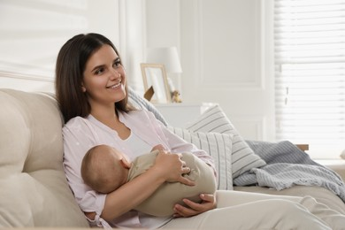 Young woman with her sleeping baby on sofa at home