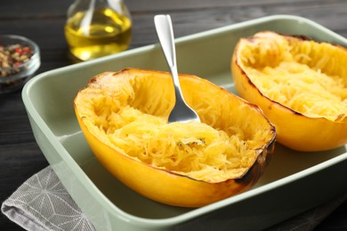 Halves of cooked spaghetti squash and fork in baking dish on table, closeup
