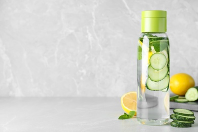 Bottle of refreshing water with cucumber, lemon and mint on light grey table, space for text