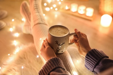 Woman with cup of drink on floor against blurred Christmas lights, closeup