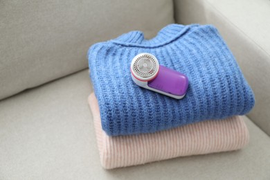 Modern fabric shaver and woolen sweaters on sofa indoors