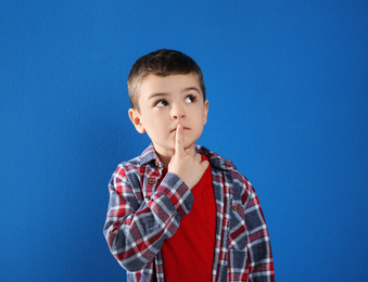 Thoughtful little boy in casual outfit on blue background