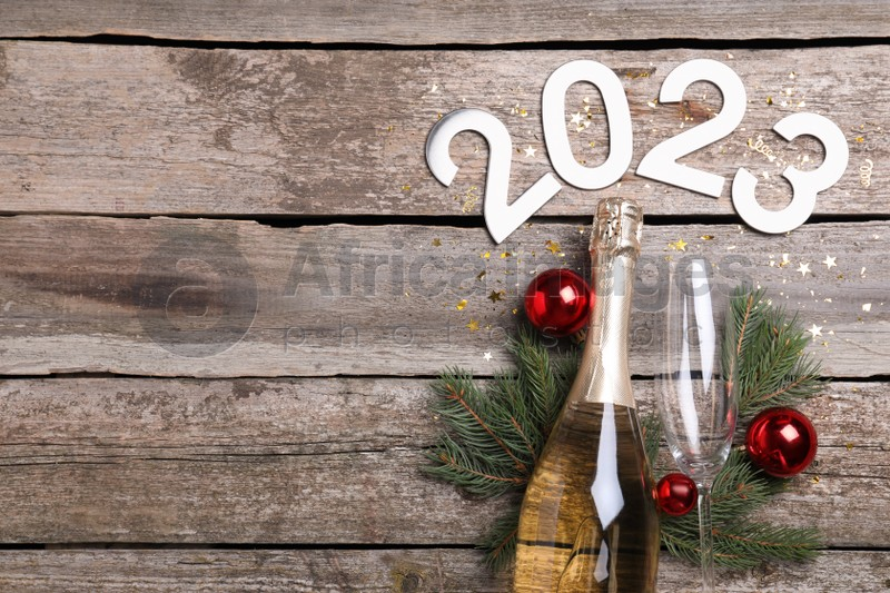 Happy New Year 2023! Flat lay composition with bottle of sparkling wine on wooden table, space for text