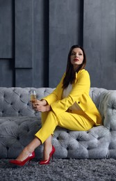 Beautiful businesswoman with glass of champagne on sofa indoors. Luxury lifestyle
