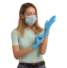 Young woman in protective face mask putting on medical gloves against white background