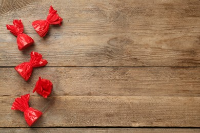 Candies in red wrappers on wooden table, flat lay. Space for text