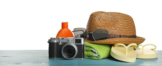 Different beach objects on turquoise wooden table against white background