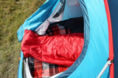 Red sleeping bag in camping tent on green grass outdoors, above view
