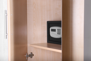 Black steel safe with electronic lock in wooden closet at hotel