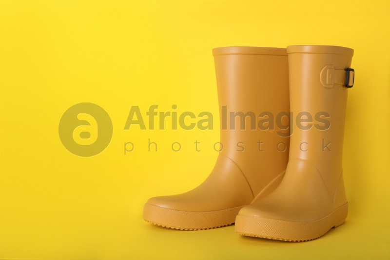 Pair of bright rubber boots on yellow background.  Space for text