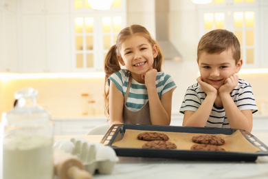 Cute little children with fresh delicious cookies in kitchen. Cooking together