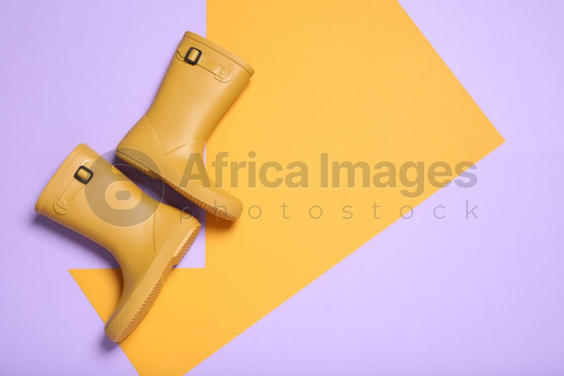 Pair of yellow rubber boots on color background, top view. Space for text