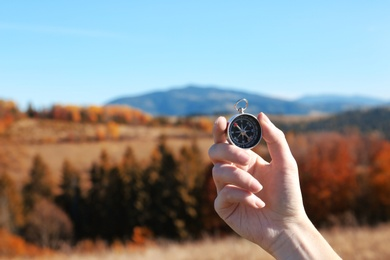 Traveler searching direction with compass in wilderness, closeup. Space for text