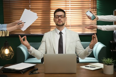 Calm businessman meditating at office desk in middle of busy work day
