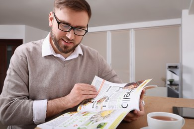 Young man reading healthy food magazine at table indoors