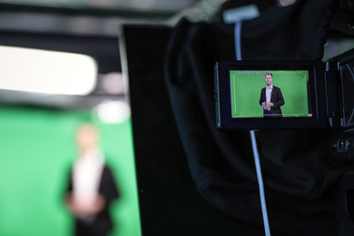Presenter working in studio, focus on video camera screen
