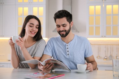 Young couple with cups of drink reading magazine at table in kitchen
