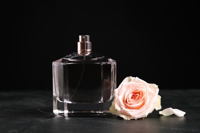 Bottle of perfume and beautiful rose on black table