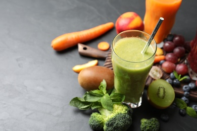 Delicious colorful juice in glass and fresh ingredients on black table, space for text