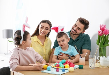 Happy family with Easter eggs at home. Festive tradition