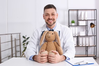 Pediatrician with toy bunny at desk in office