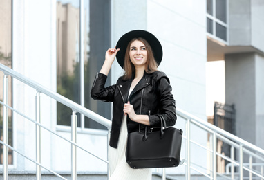 Beautiful young woman with stylish leather bag outdoors