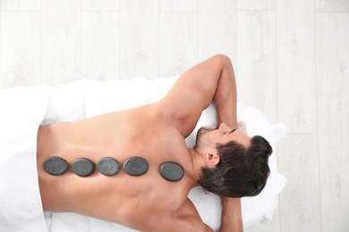 Young man receiving hot stone massage in spa salon, top view. Space for text