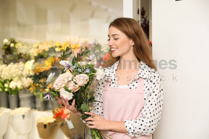 Professional florist with bouquet of fresh flowers in shop