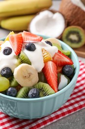 Delicious fruit salad with yogurt on table