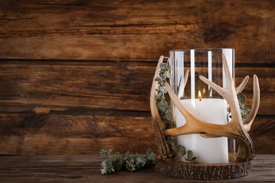 Elegant holder with candle on wooden table. Space for text
