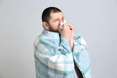 Man with plaid suffering from runny nose on light grey background
