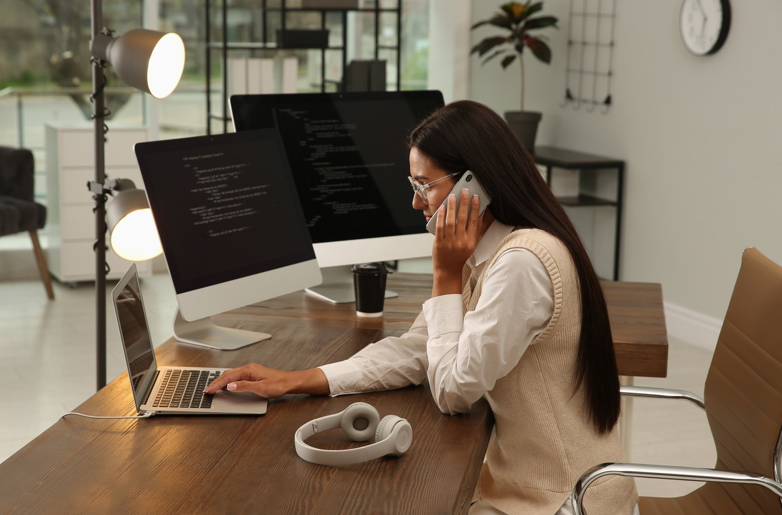 Programmer talking on phone while working at desk in office