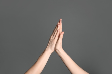 Women giving high five on grey background, closeup. Victory concept